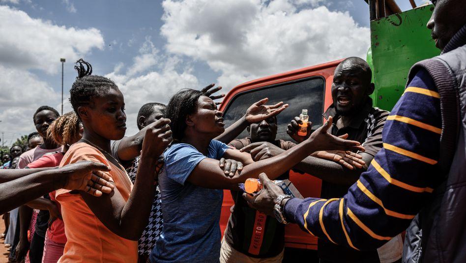 Menschen im Kibera Slum in Nairobi, Kenia, stehen Schlange für Mehl, Bohnen und Milch. Die Lebensmittel werden von der lokalen Hilfsorganisation Team Pangaj ausgegeben