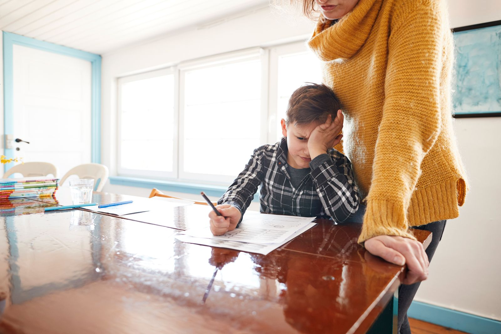 Mother watching frustrated son doing homework at dining table