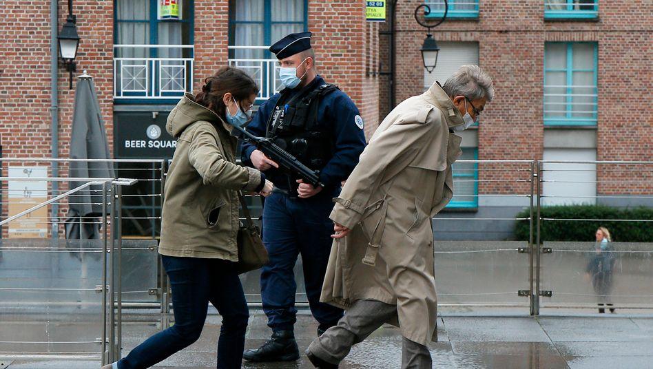 Passanten, bewaffneter Polizist vor der Kathedrale in Lille