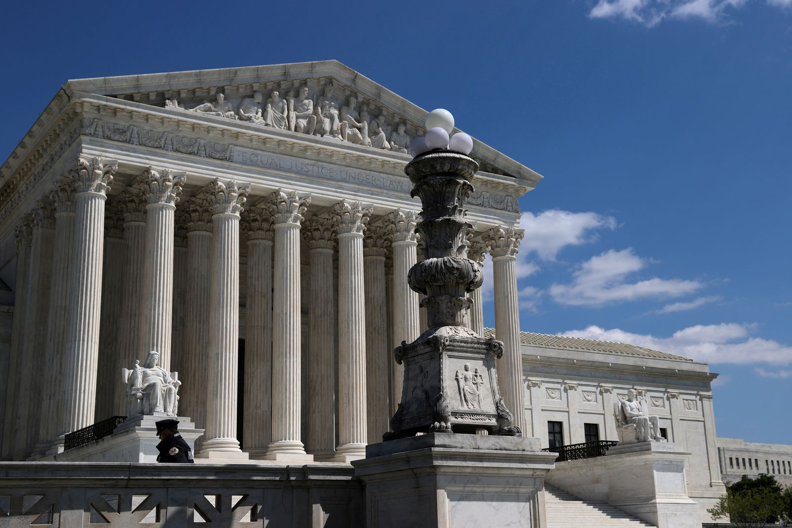 FILE PHOTO: A police officer is mostly alone on the plaza in front of the U.S. Supreme Court building during the coronavirus disease (COVID-19) outbreak in Washington