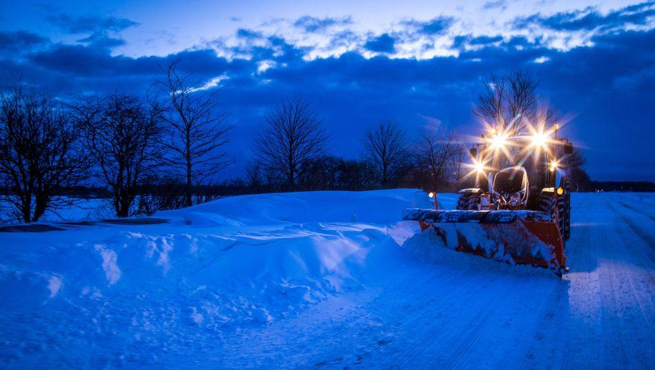 Ein Traktor mit Schneepflug Mecklenburg-Vorpommern: Frostige Temperaturen und Schneefälle behindern den Verkehr in Norddeutschland