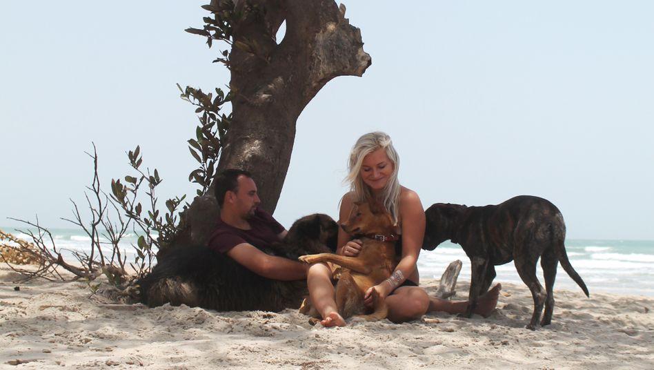 Janine Hölscher mit ihrem Freund Aaron und ihren Hunden am Strand in Gambia