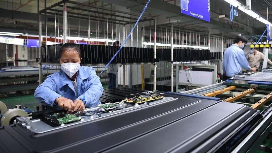 Angestellte arbeiten mit Mundschutz in einer Fernseherfabrik von Skyworth im chinesischen Guangzhou