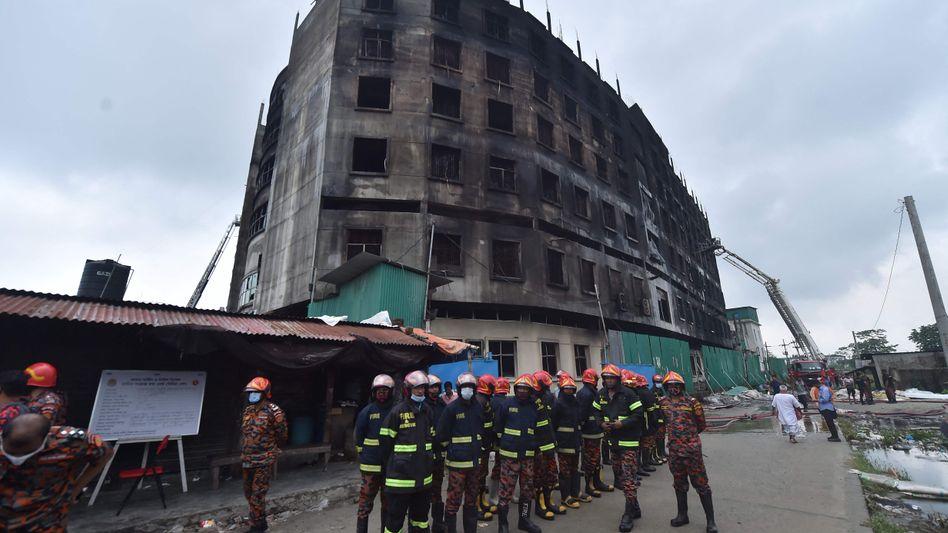 Feuerwehrleute vor dem ausgebrannten Fabrikgebäude in Rupganj