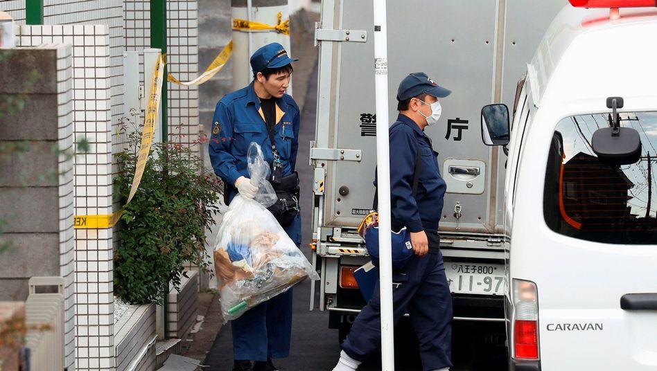 Ein Polizeibeamter trägt eine Plastiktüte aus der Wohnung des jungen Manns