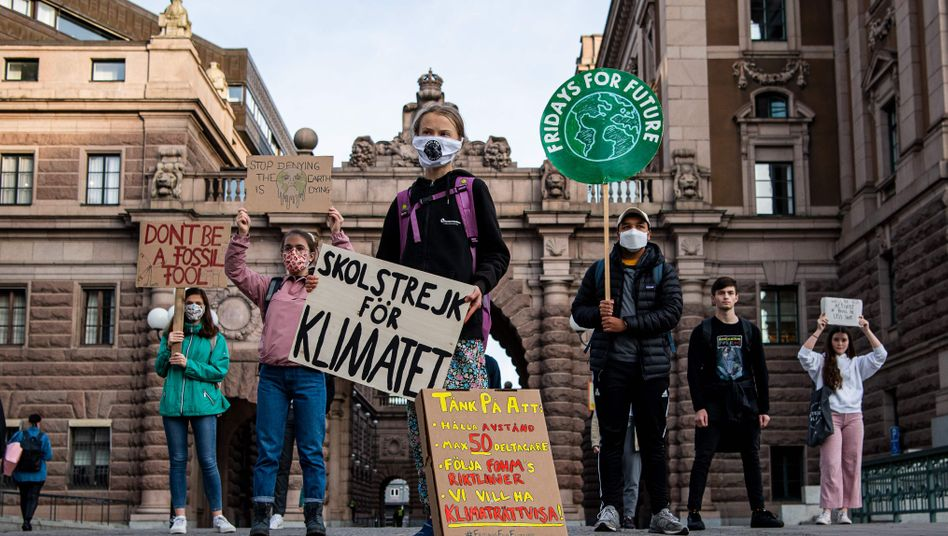 """Greta Thunberg: Neben ihrem berühmt gewordenen Protestschild mit der Aufschrift """"Skolstrejk för klimatet"""" (Schulstreik fürs Klima) erinnert die Aktivistin auf einem zweiten Plakat an die Corona-Regeln"""