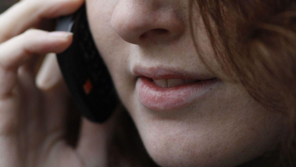 """Frau mit Mobiltelefon am Ohr: Strahlen """"möglicherweise krebserregend"""""""