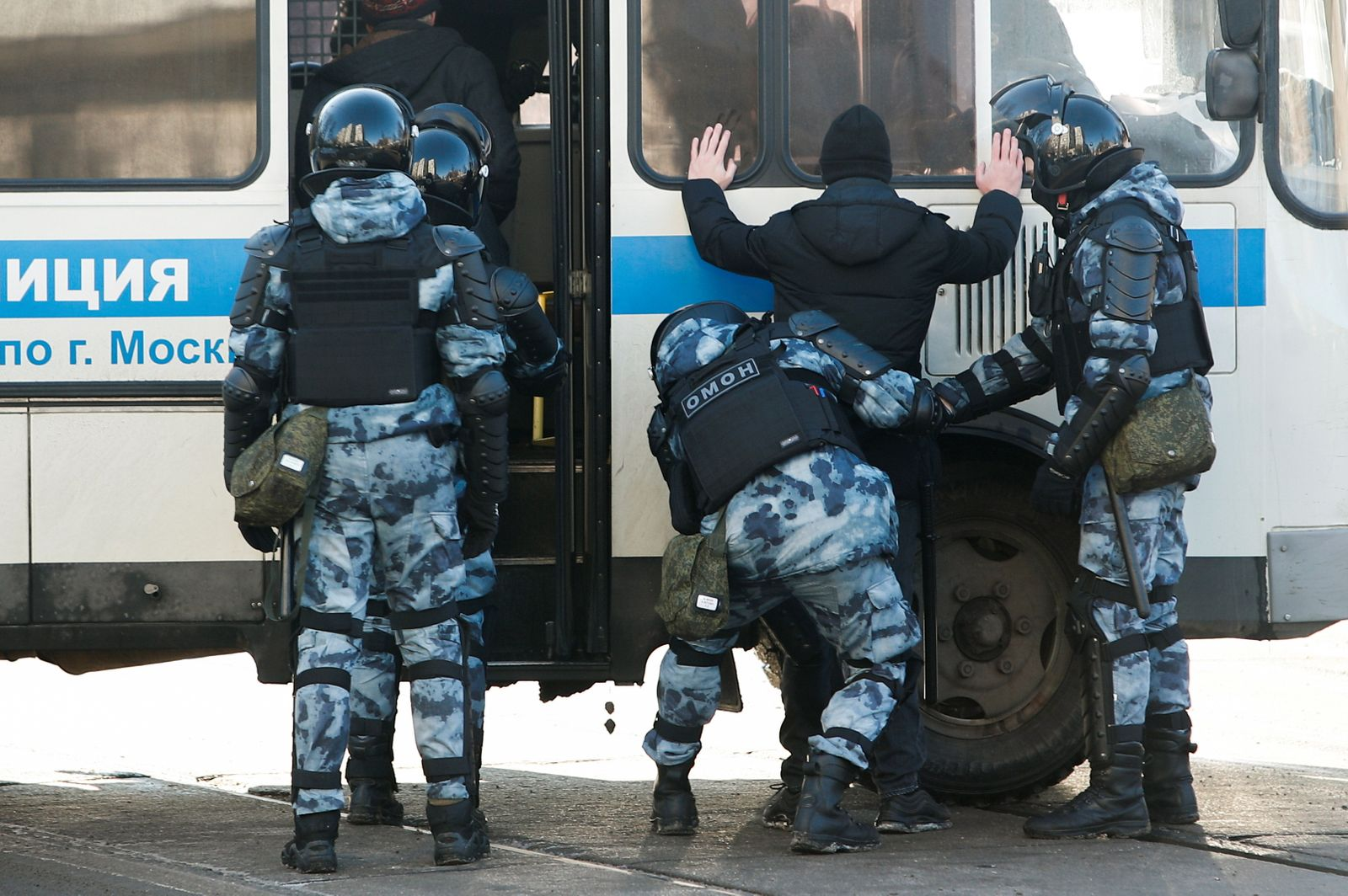 Law enforcement officers detain a man near a court building during a hearing in case of Russian opposition leader Alexei Navalny in Moscow