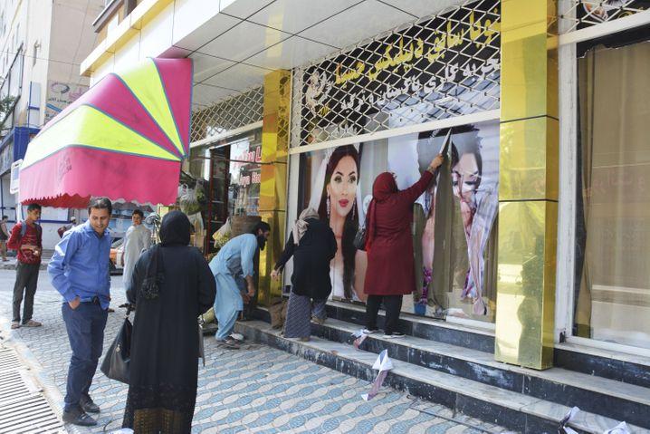 Arbeiter in einem Schönheitssalon entfernen am 15. August in Kabul große Fotos von Frauen von der Wand, nachdem die Taliban in die afghanische Hauptstadt eingedrungen sind