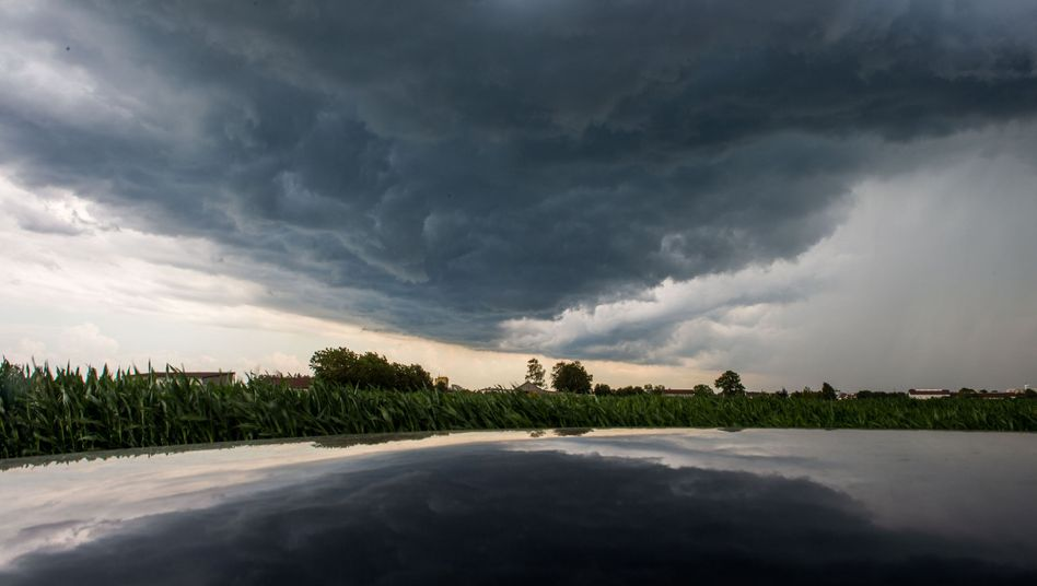 Gewitterwolke spiegelt sich in einem Autodach (Archiv)