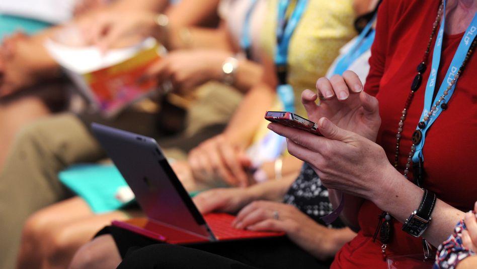 Frauen mit Smartphone und Laptop auf der Konferenz DLD Women