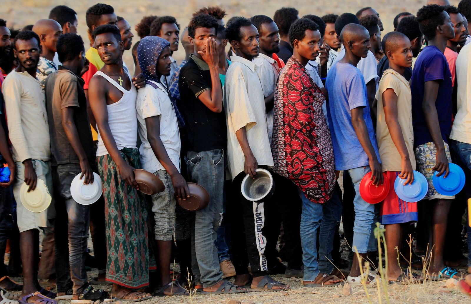 Ethiopian men who fled war in Tigray region, queue for wet food ration at the Um-Rakoba camp, on the Sudan-Ethiopia border in Al-Qadarif state