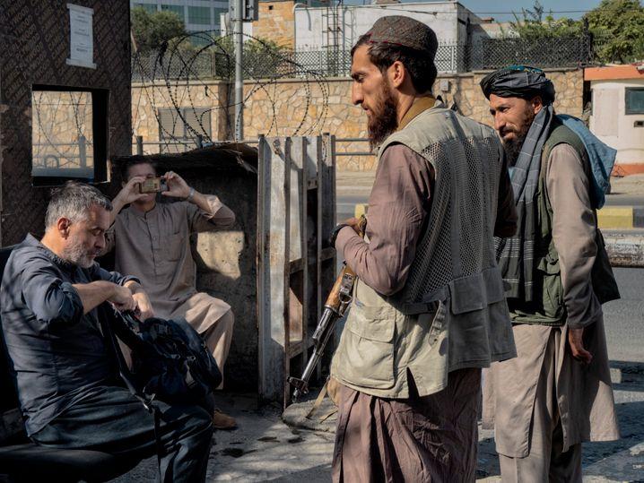 Reuter (l.) mit Taliban vor der deutschen Botschaft
