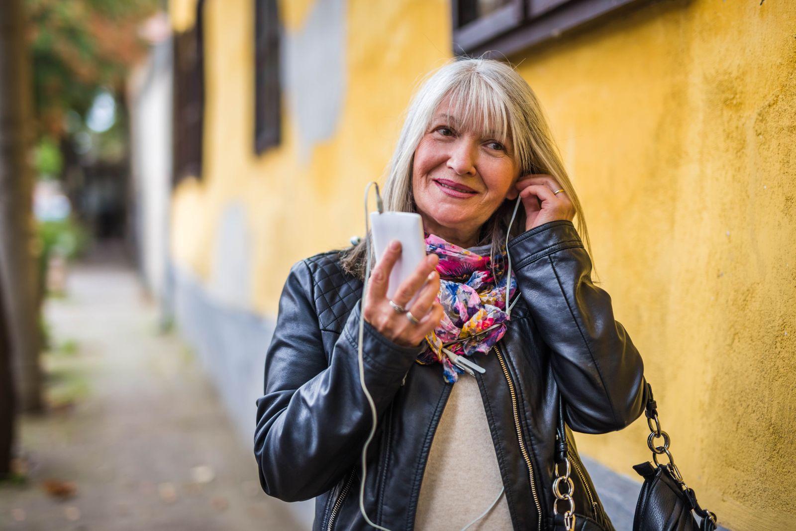 Happy older woman listening music