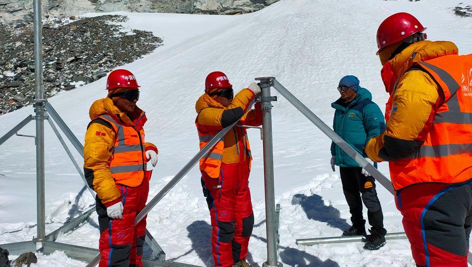 Mitarbeiter des chinesischen Mobilfunkproviders China Mobile errichten in der Nähe des Mount Qomolangma Base Camp eine 5G-Basisstation