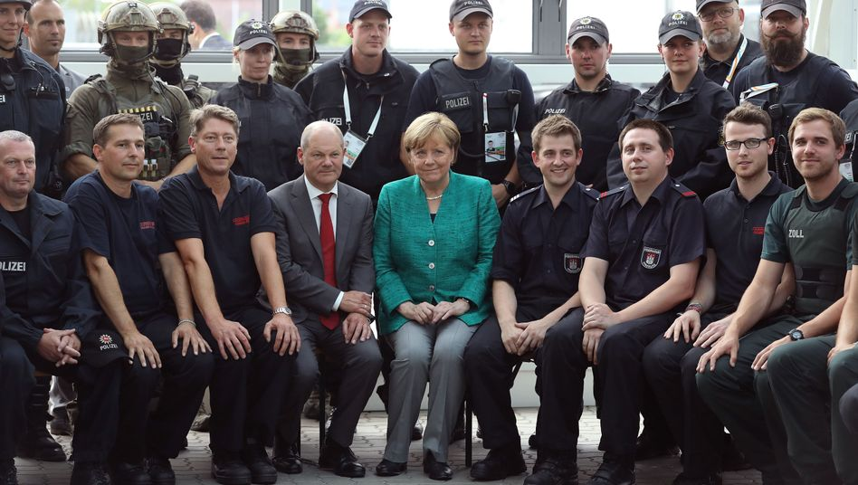 Chancellor Angela Merkel and Hamburg Mayor Olaf Scholz with G-20 security personnel