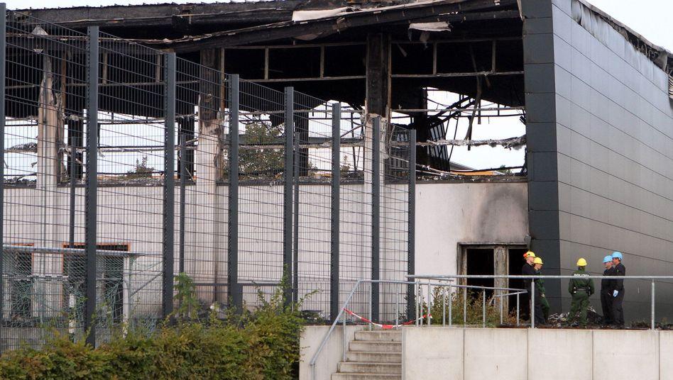 Polizisten vor der abgebrannten Halle: Bisher keine Hinweise auf Täter