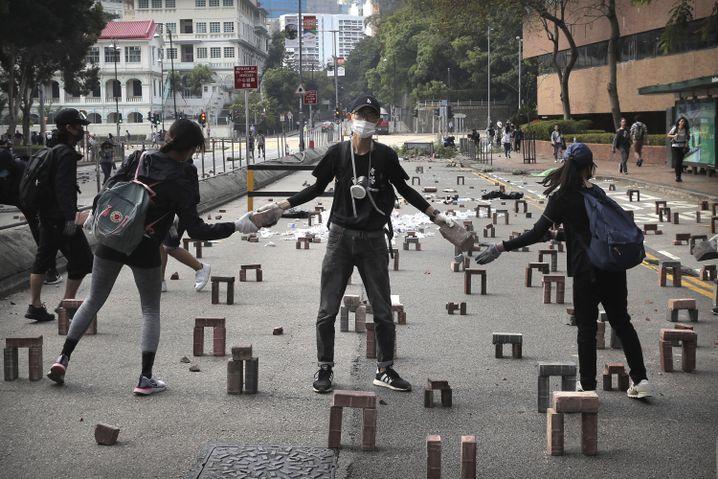 Demonstranten reichen Steine weiter, um eine Straße nahe der Universität zu blockieren