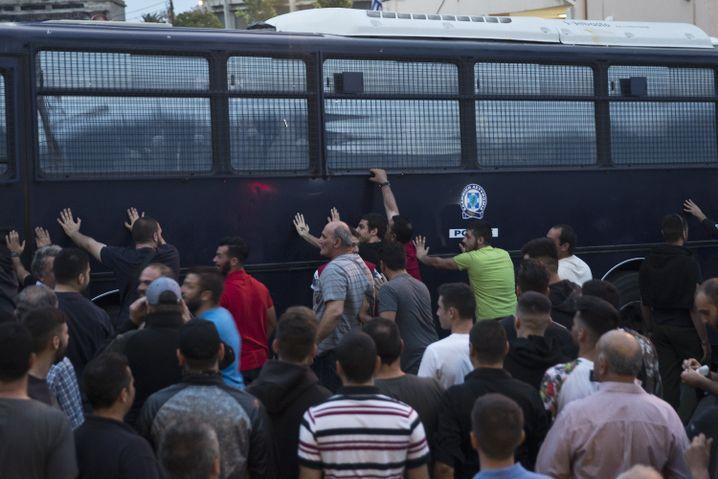 Männer versuchen während einer Demonstration auf Lesbos einen Polizeibus umzuwerfen.