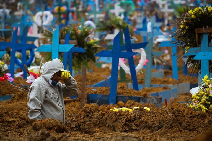 Ein Mann arbeitet an einem Massengrab in Manaus