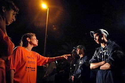 Protest gegen die Zwangsräumung: jüdische Siedler debattieren mit israelischen Soldaten