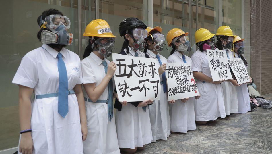 Schülerinnen tragen Gasmasken und Helme bei Protesten im St. Francis Canossian College