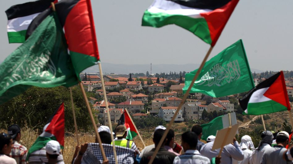 Demonstrators waving the flags of Hamas and the Palestinian Territories.