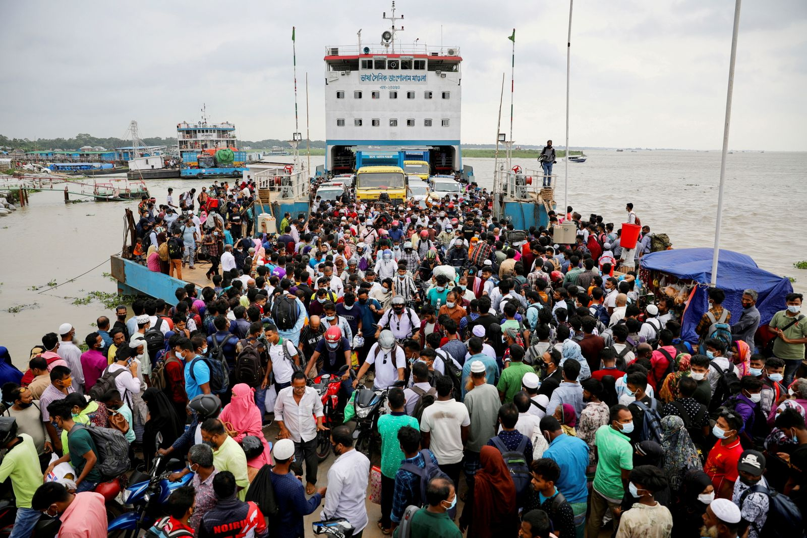 People board an overcrowded ferry as they go home a day before imposing a countrywide lockdown in Munshiganj, outskirts of Dhaka
