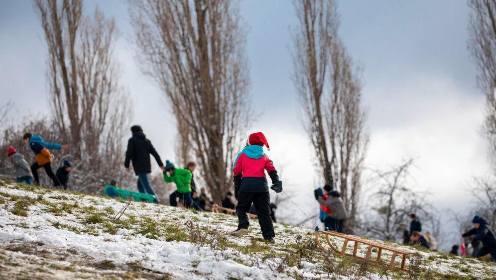 In einem Park in Berlin sind Kinder und Erwachsene mit Schlitten unterwegs