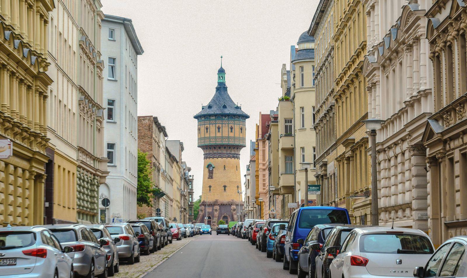 Strassenzug mit prachtvollen Hausfassaden aus der Gruenderzeit und historischem Wasserturm in Halle an der Saale. *** St