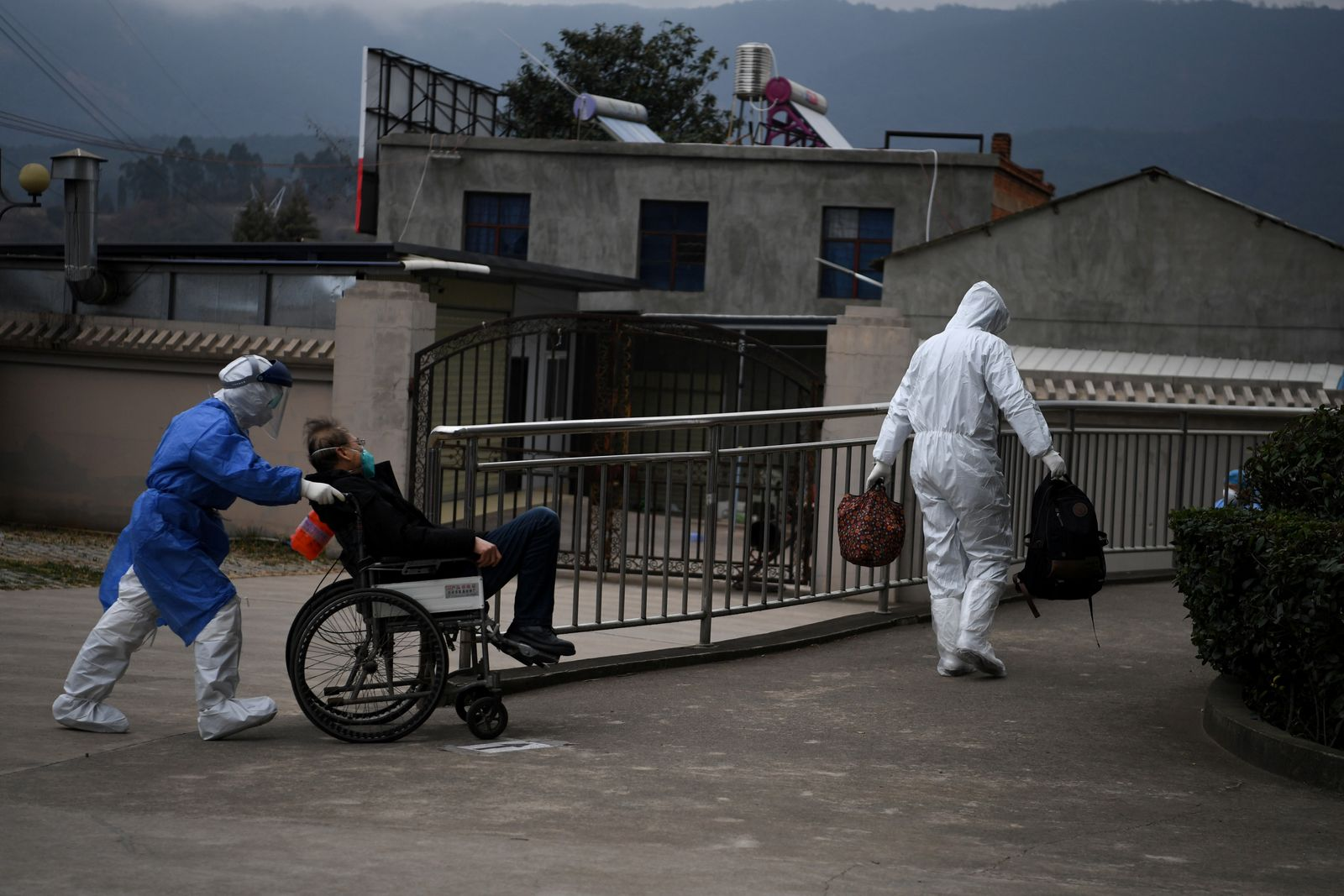 Members of a medical team tasked to transfer suspected or confirmed novel coronavirus patients to designated treatment sites transport a man in a wheelchair in Kunming