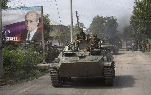 Ossetian soldiers on top of a tank enter Tskhinvali next to a giant portrait of Russian Prime Minister Vladimir Putin.