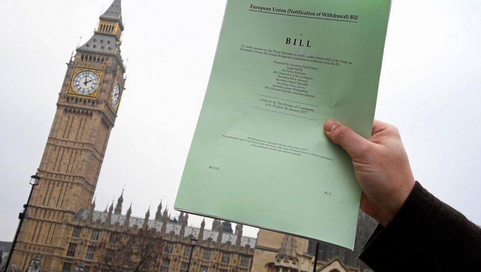 A copy of the British Article 50 bill is held up in front of parliament.