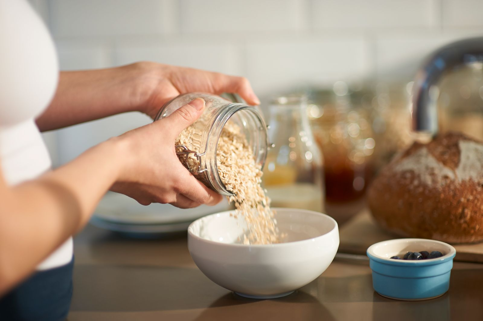 Woman pouring oats into bowl in kitchen, close up.