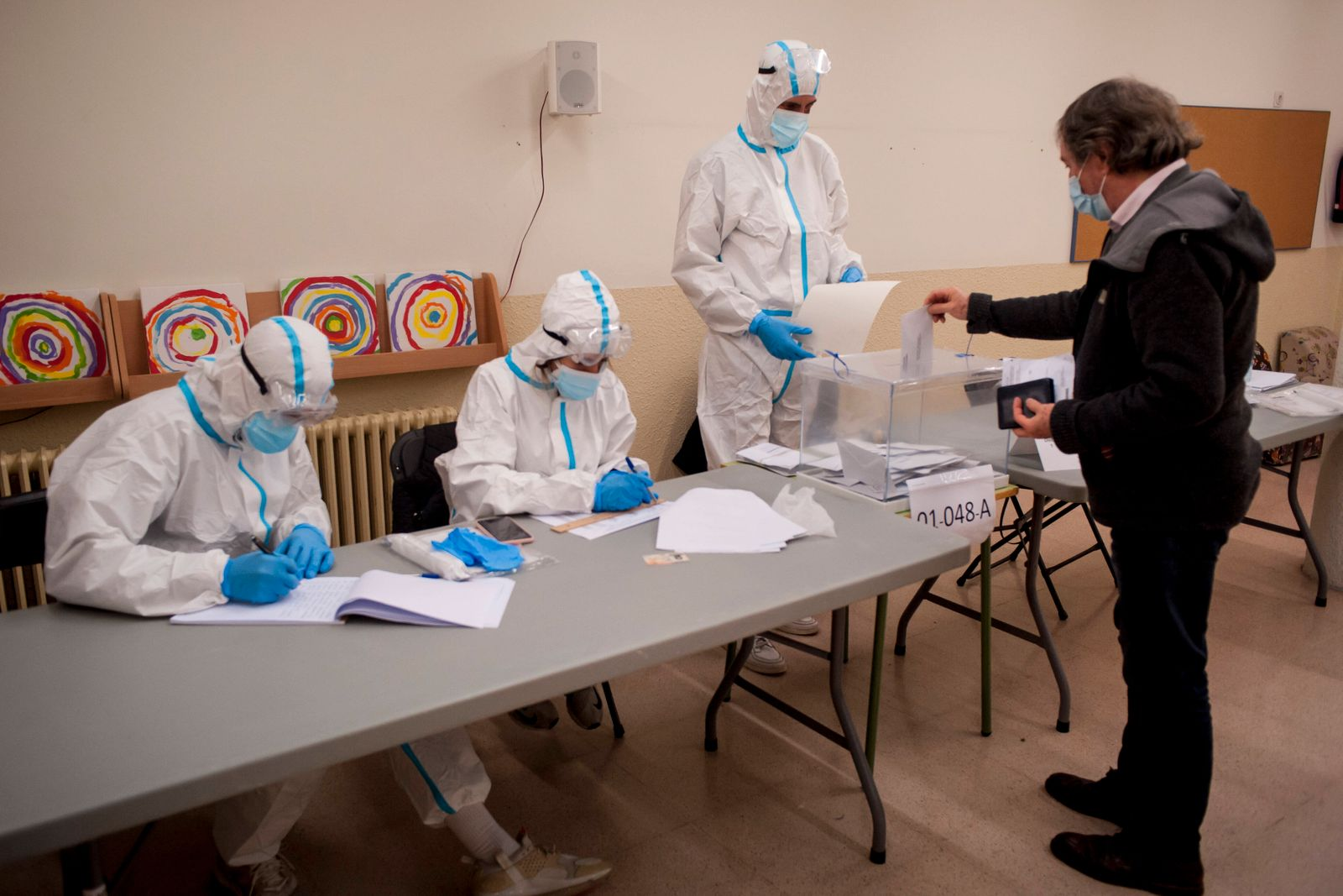 February 14, 2021, Barcelona, Catalonia, Spain: A man casts his vote in a polling station of Barcelona with workers wea