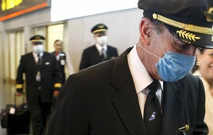 The crew of a plane that has arrived from Mexico wears face masks as they arrive at Madrid's Barajas airport on Monday.