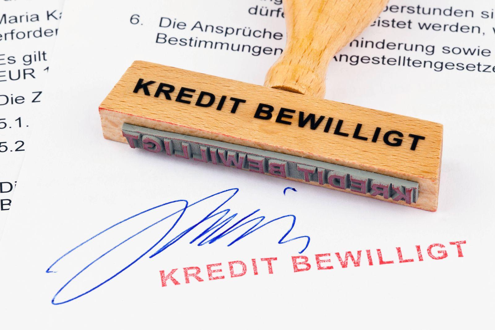 Ein Stempel aus Holz liegt auf einem Dokument Aufschrift Kredit bewilligt McPBBO McPBBO