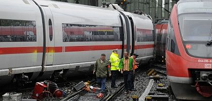 Police and employees of Deutsche Bahn investigate a derailed high-speed train in Cologne.