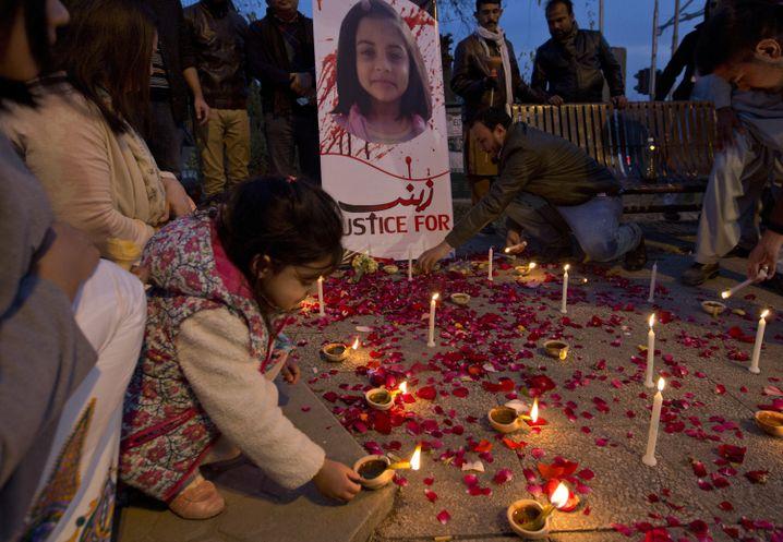 Ein Mädchen stellt eine Kerze für die ermordete Zainab auf