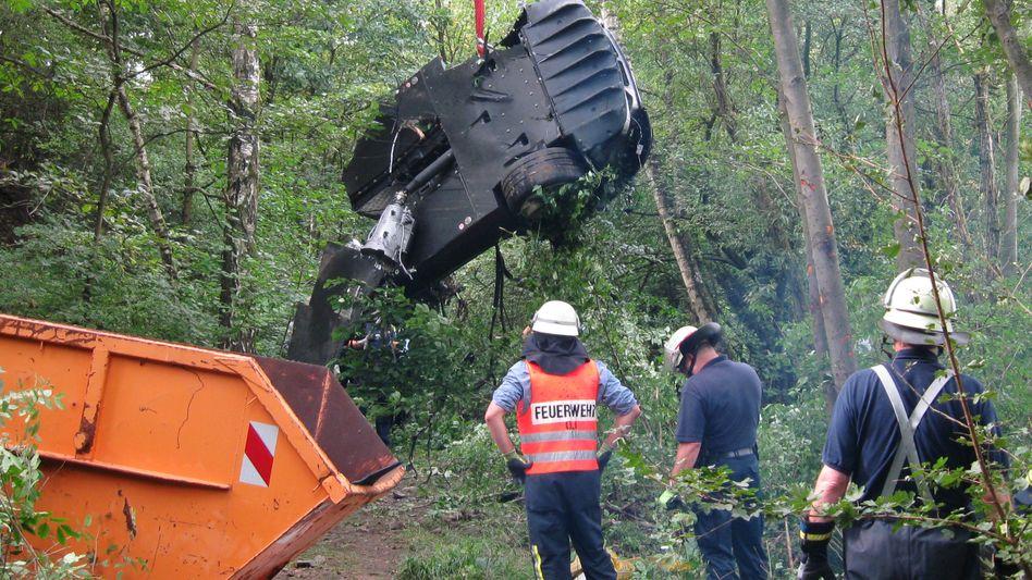 Unfallstelle bei Kelkheim: Feuerwehrleute bergen das Wrack eines Mercedes SLR McLaren