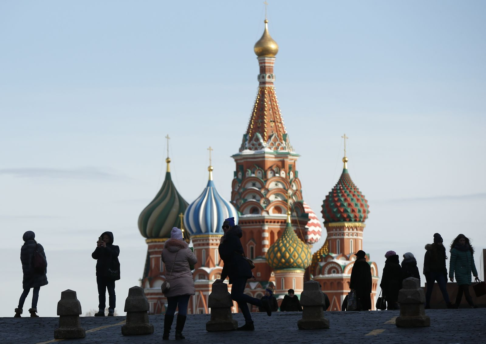 People take pictures next to St. Basil's Cathedral at Red Square in Moscow