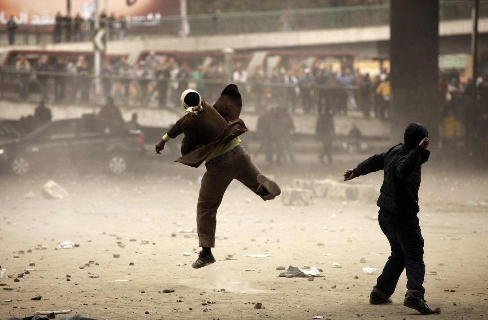 Egyptian demonstrators throw stones