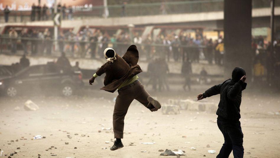 Egyptian demonstrators throw stones in Cairo on Thursday.