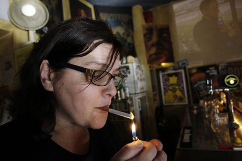 Sylvia Thimm lighting up in her bar in Berlin. Her complaint against the smoking ban was upheld on Wednesday.