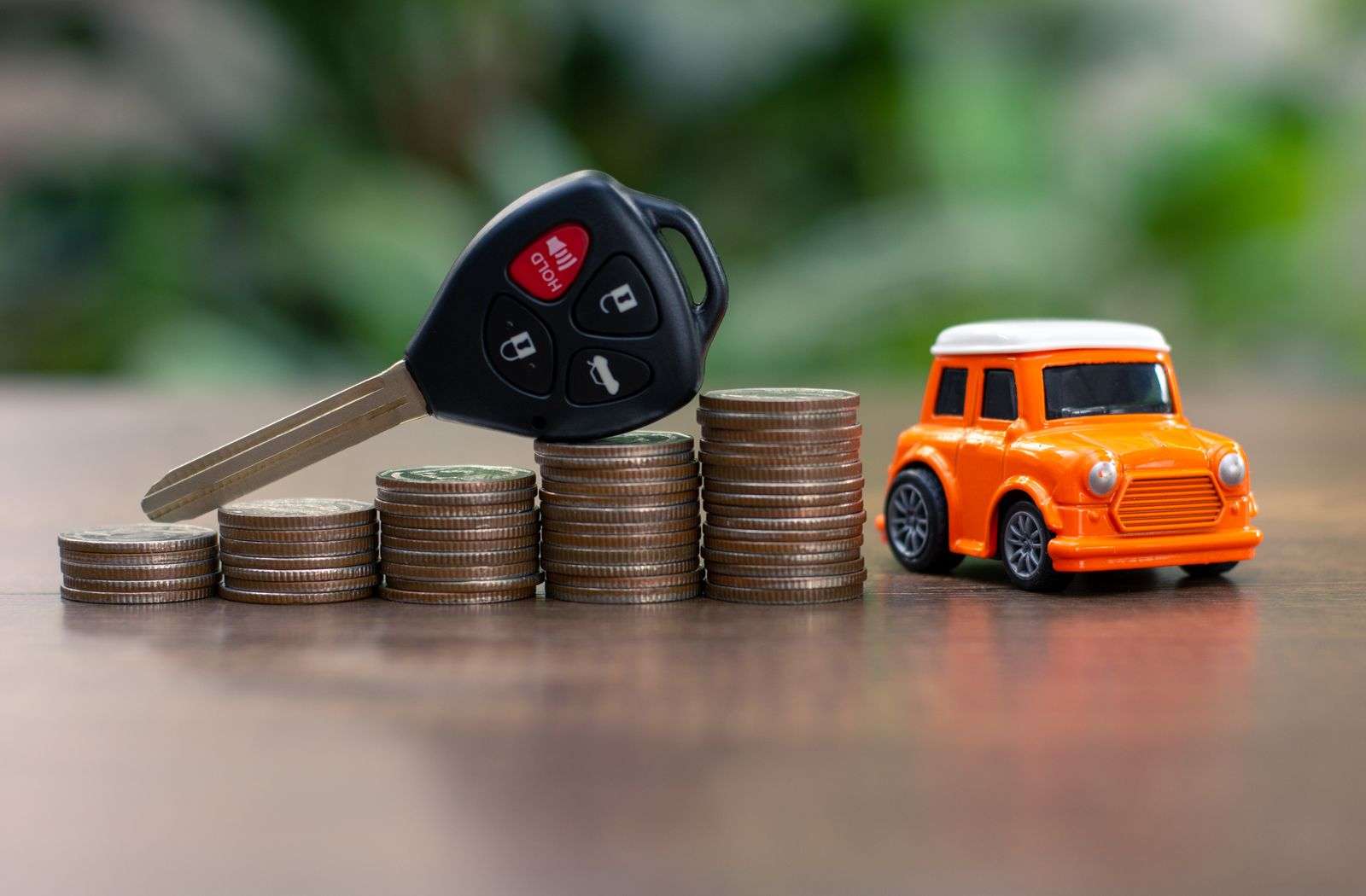 Car key on money coin with car model on table, Sell and Buy car concept.