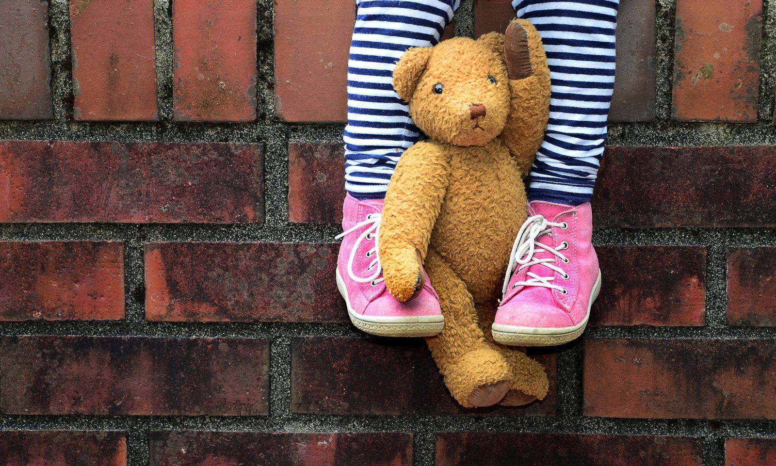 Teddy zwischen die Beine geklemmt Kind sitzt auf Mauer Detail Deutschland Europa Copyright imag