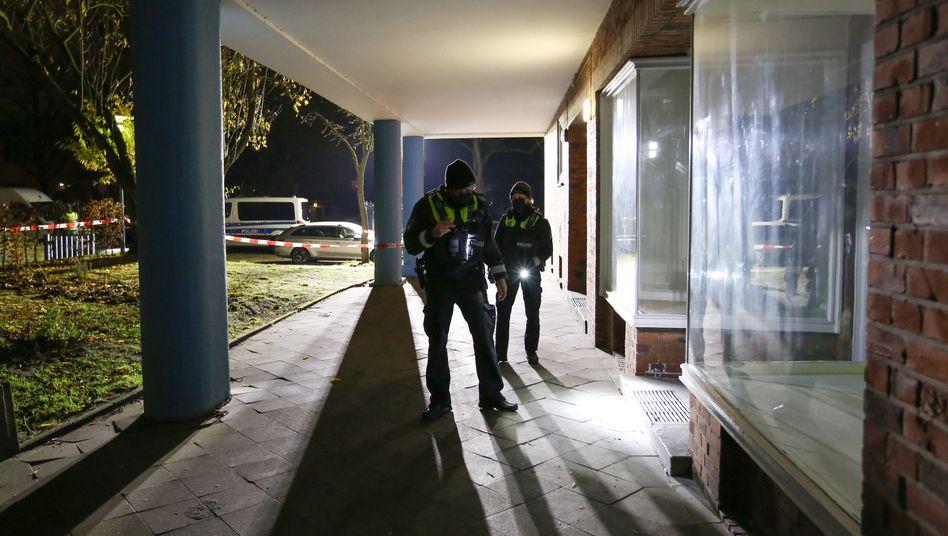 Hamburg-Altona: Polizisten suchen in der Nähe eines Tatortes mit Taschenlampen nach Beweismitteln.