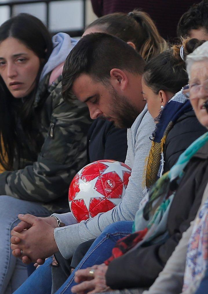 Julens Eltern mit einem Ball des Jungen im Friedhofsgebäude