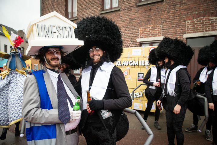 Belgischer Humor: Unesco-Bonze und ein Mann mit Insektenkostüm, Schläfenlocken und Schtreimel in Aalst