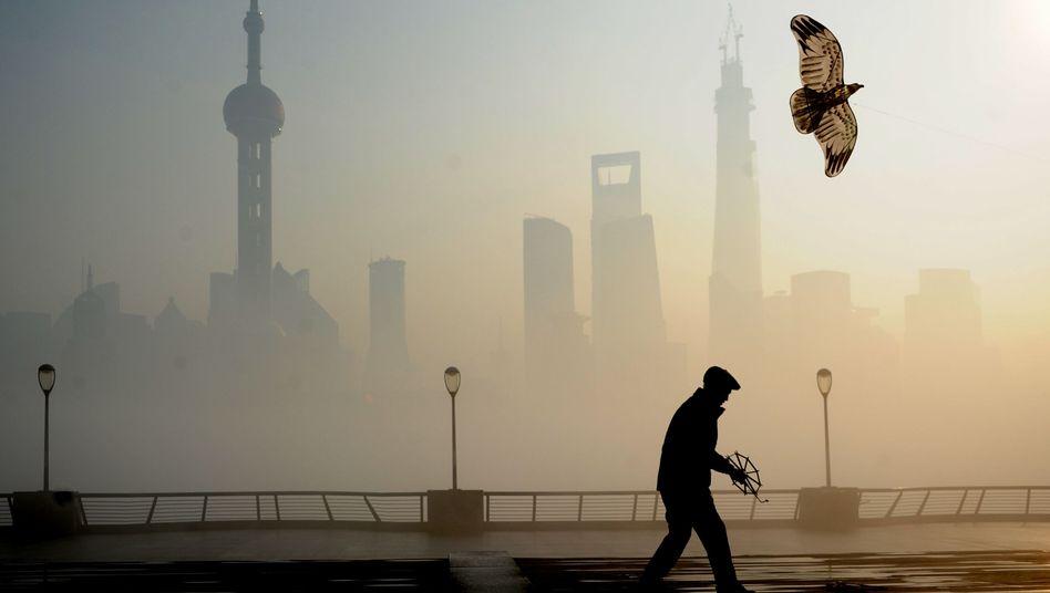 Mann beim Drachensteigenlassen im Smog von Shanghai: 2,5 Milliarden Jahre an Lebenserwartung verloren